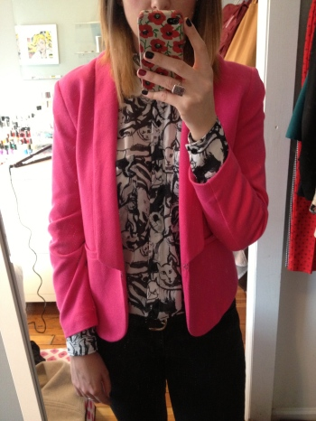 Pink cropped blazer with a cat-printed top and black jeans.